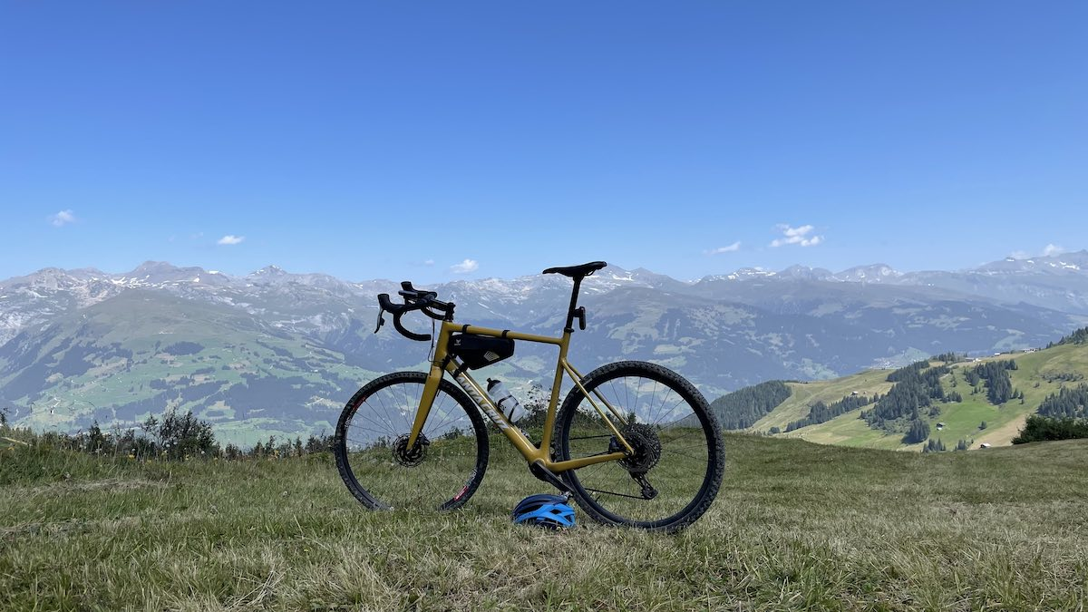 bikerumor pic of the day a bicycle is on a grassy ridge overlooking the alps in switzerland the sky is clear and blue and the mountains in the distance are speckled with clusters of forest and open grassland.