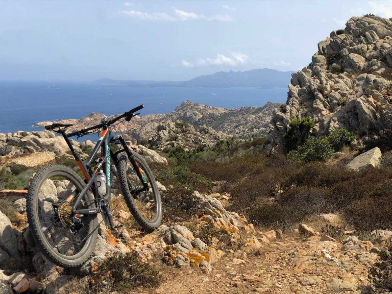 bikerumor pic of the day a mountain bike leans agains a large outcropping of jagged rock on the island of Cabrera off the coast of italy, the ocean is down in the distance and the sun is high overhead.