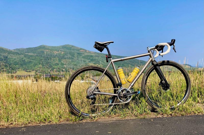 bikerumor pic of the day a bicycle is on the side of a road in golden brush with a gentle sloping green mountain in the background, the sky is clear and blue.