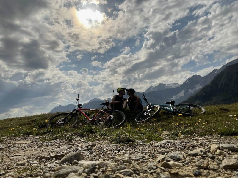 bikerumor pic of the day a couple sits together on the rocky ledge of a mountain with their mountain bikes laid at their feet, the sky is partly cloudy and the sun is strong behind them.