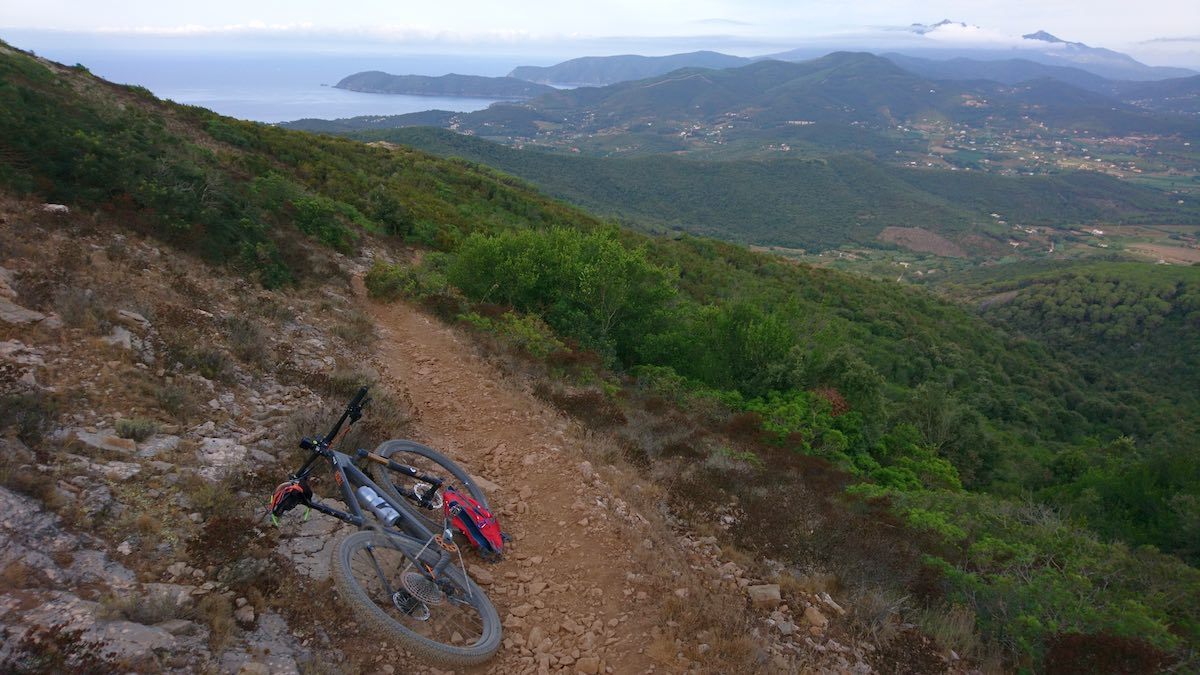 bikerumor pic of the day a mountain bike leans on the side of a dirt trail on the side of a mountain overlooking the rest of the island with a body of water in the distance.