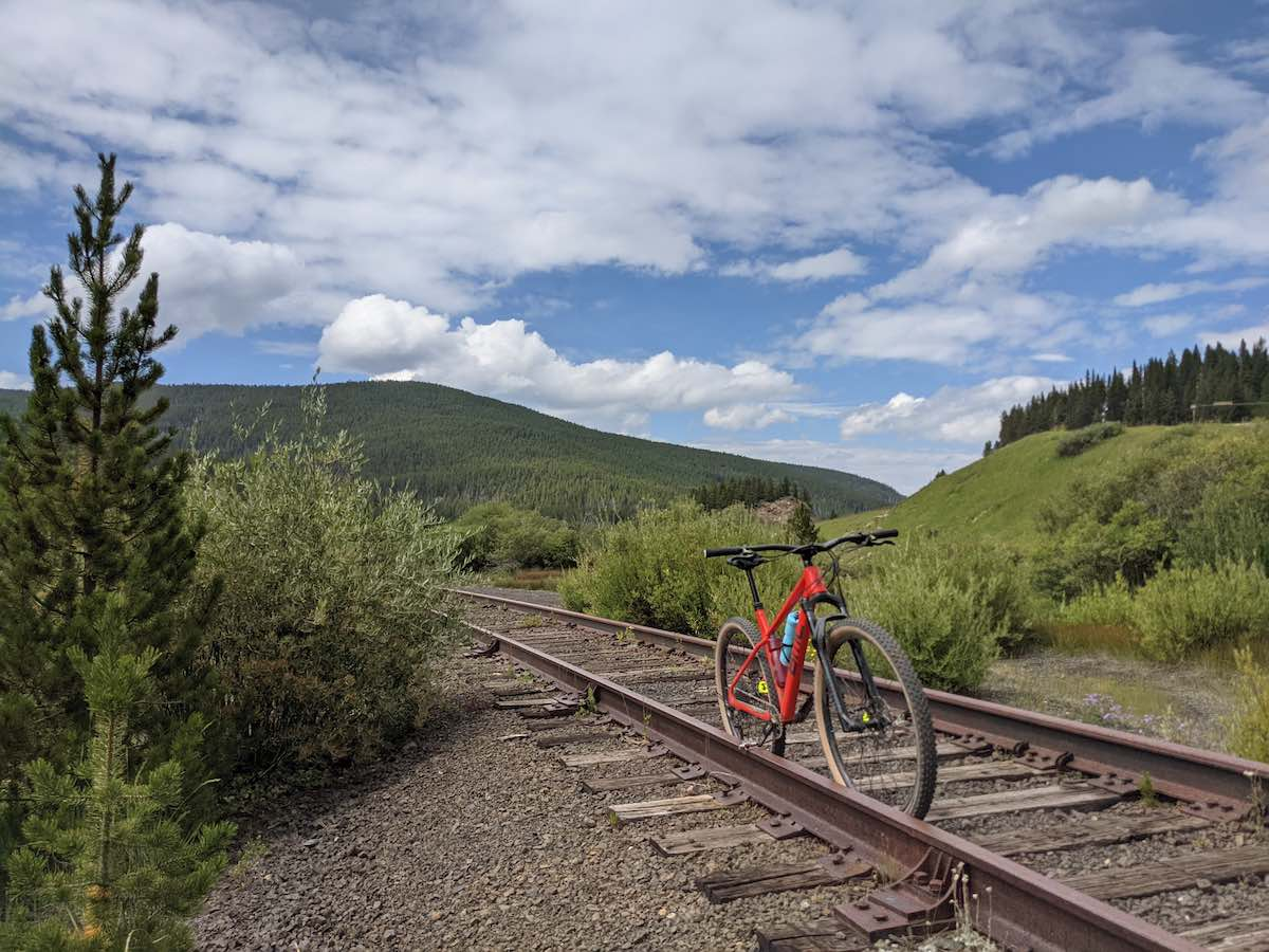 bikerumor pic of the day a red mountain bike is on an old trail rail line in colorado with sage brush on either side and a mountain in the distance, the sky is blue with fluffy clouds.
