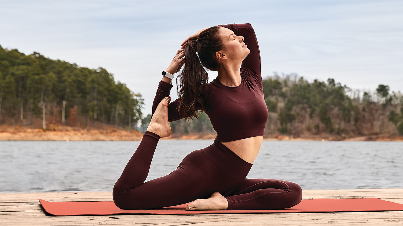 girl doing yoga with the fitbit charge 5 smartwatch fitness tracker