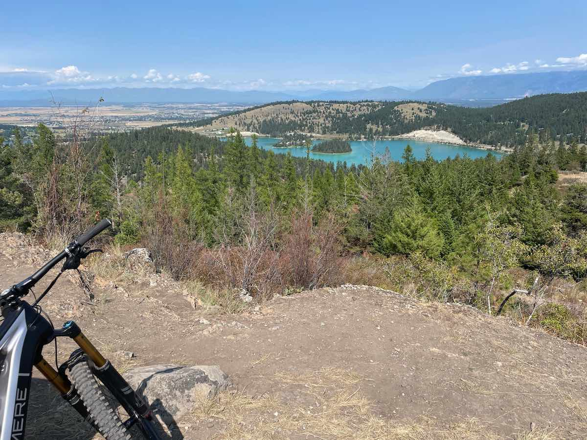 bikerumor pic of the day a bike is seen in the corner of the picture on a dirt landing overlooking a clear blue lake on the side of a mountain surrounded by pine forrest and a small town in the distance, the sky is blue and the sun is high overhead.