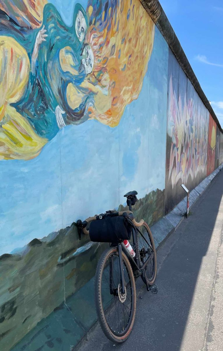 bikerumor pic of the day a bicycle leans against a piece of the former berlin wall that has been painted with colorful graffiti.