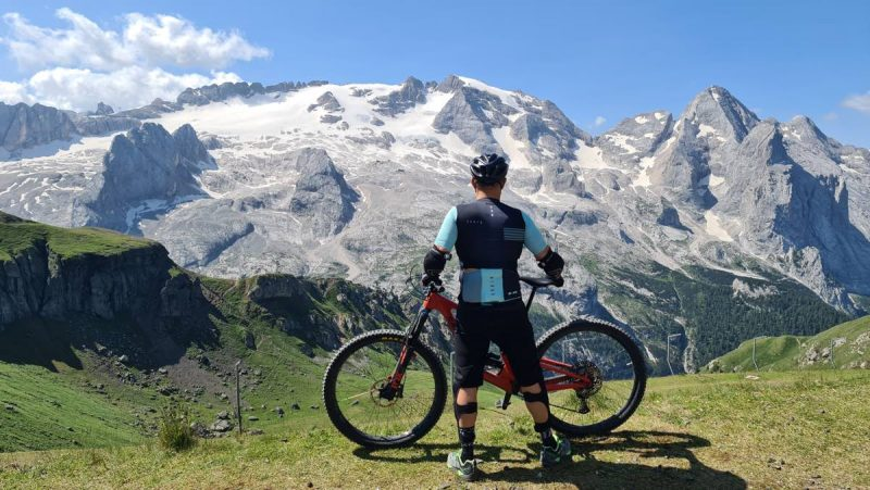 bikerumor pic of the day a cyclist stands with their bike overlooking a glacier that looks like a grey rocky mountain, the cyclist is standing on green grass and the sun is high in the sky