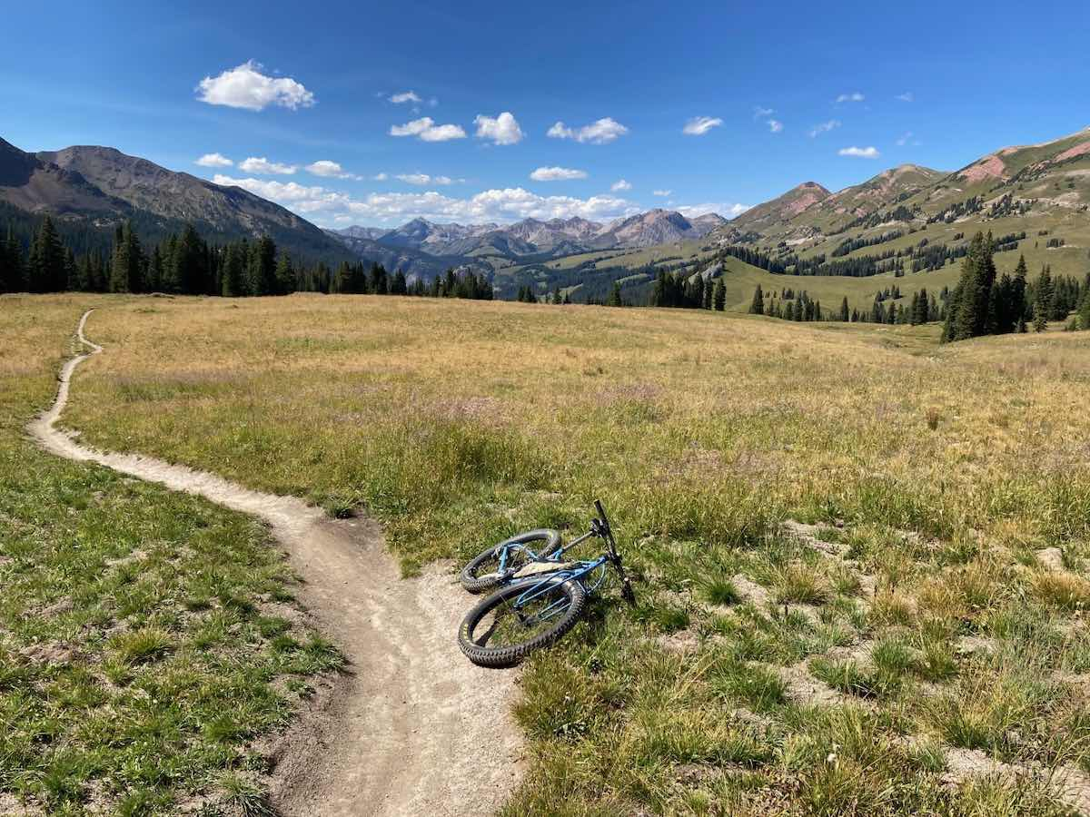 bikerumor pic of the day a mountain bike lays next to a dirt trail in the middle of a scrub grass valley, rocky mountains surround the valley, the sky is blue with a few specks of clouds, the sun is bright and overhead.