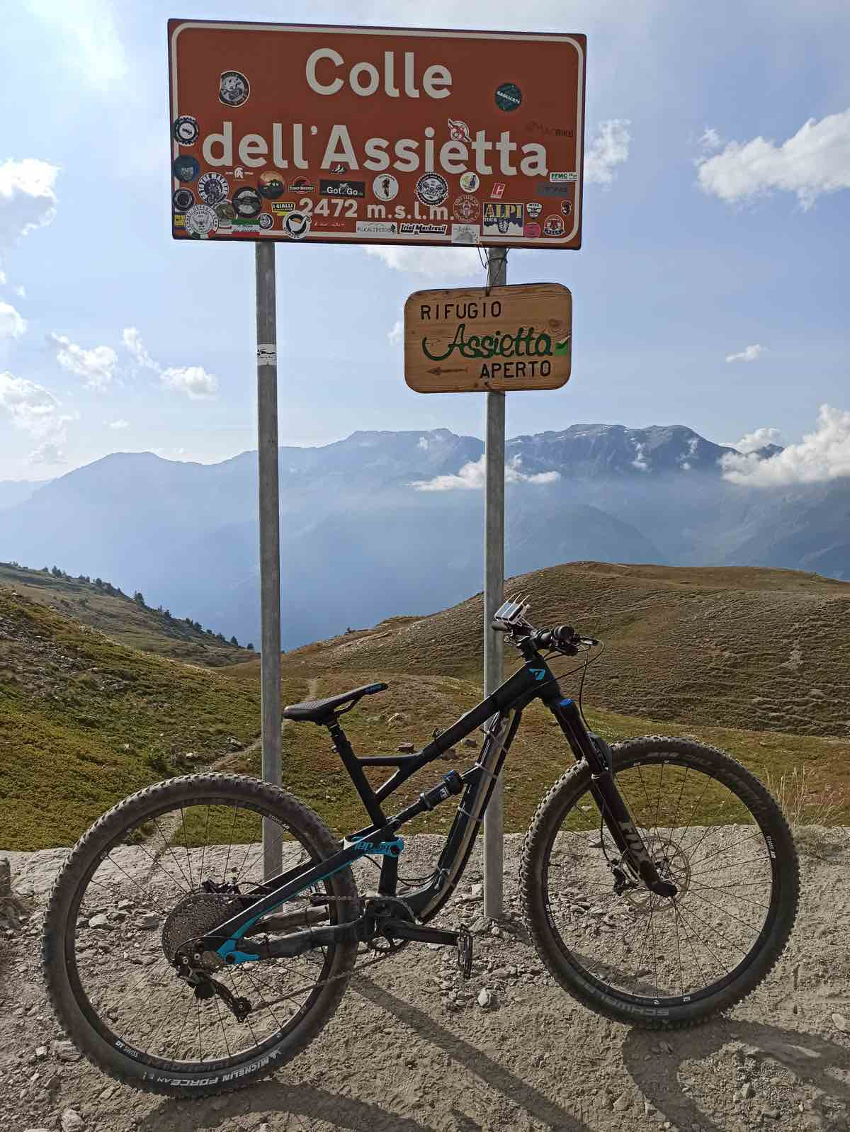 bikerumor pic of the day a mountain bike is next to a sign that says Colle dell'Assietta and a sign for a refugio on the top of a mountain pass in the alps, the mountains in the distance are covered by clouds.