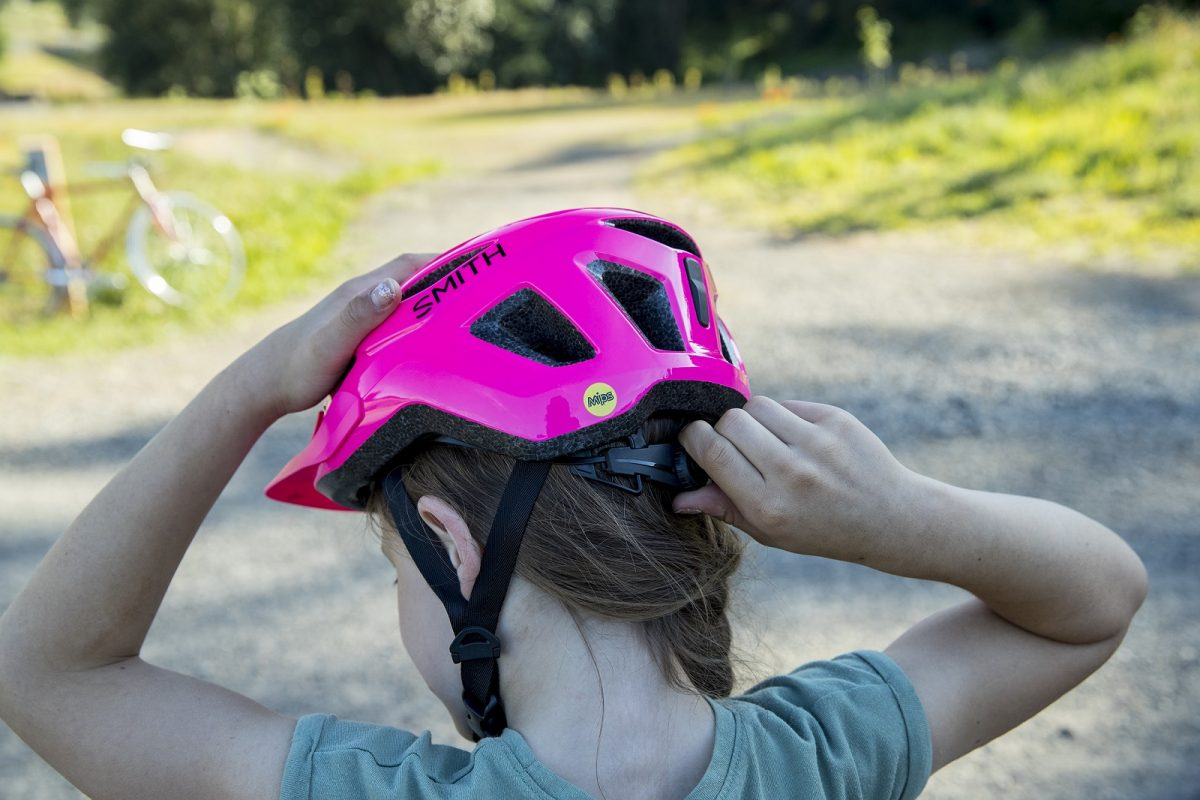 Girl adjusts the quick-fit knob on a Smith Wilder Jr. youth cycling helmet