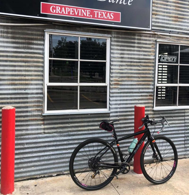 bikerumor pic of the day a bicycle leans against a short red pillar next to a building with corrugated metal siding in grapevine texas.