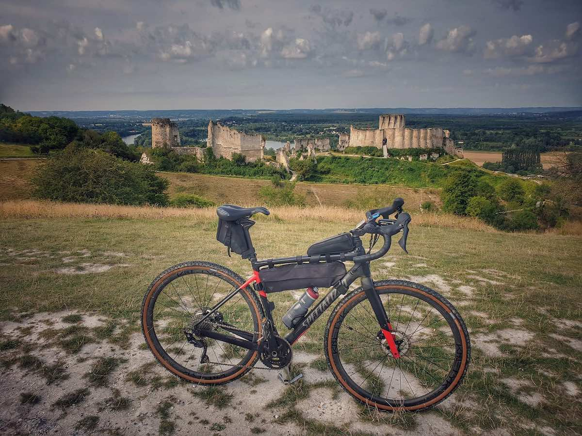 bikerumor pic of the day, a bicycle is on a low grassy hill overlooking a castle in ruins.