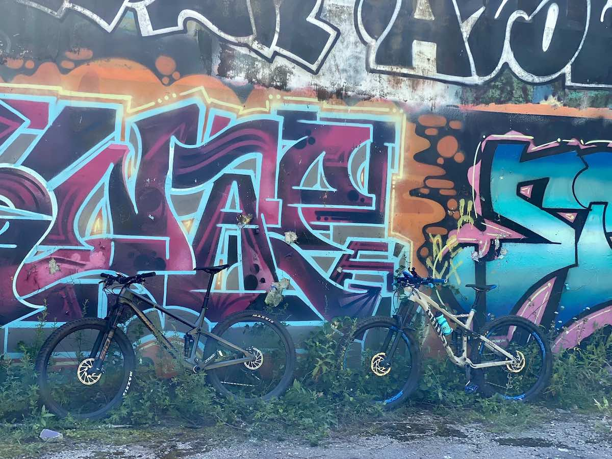 bikerumor pic of the day two mountain bikes lean against a concrete wall covered in colorful graffiti