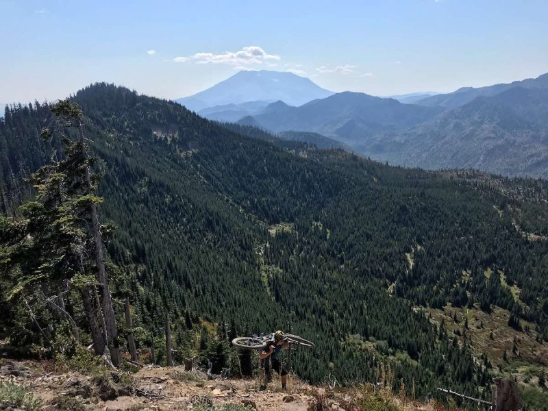 bikerumor Pic of the day a person carrying a mountain bike appears at the top of a trail with pine tree covered mountain peaks in the distance.