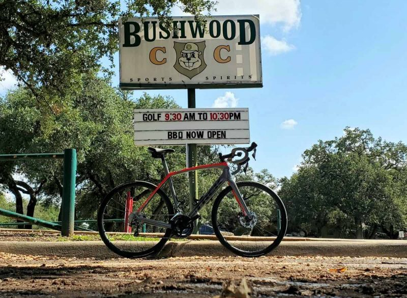 bikerumor pic of the day a bicycle is in front of a sign for brushwood country club bbq there is a picture of a gopher in the middle of the sign. the sky is blue with some clouds and there are trees in the background