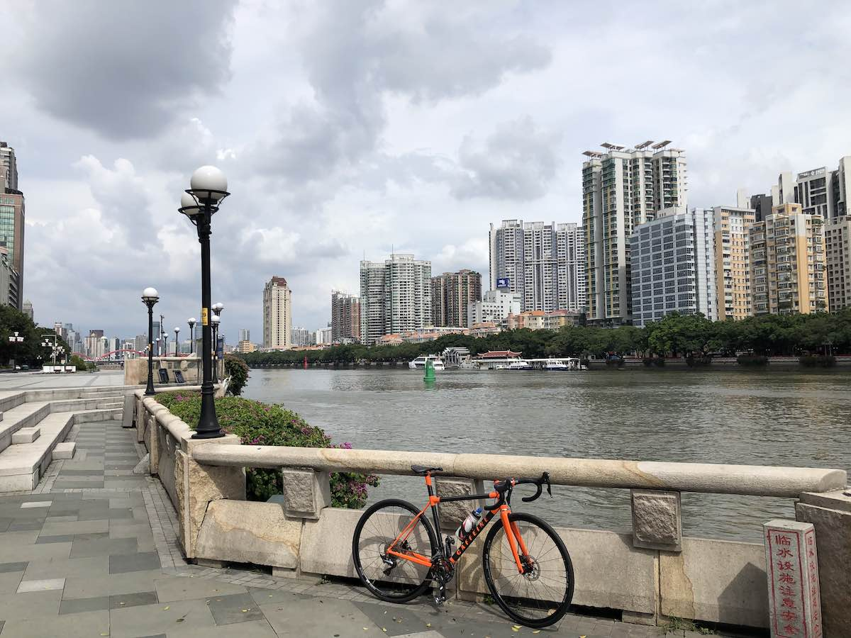 bikerumor pic of the day a red bike leans a against a concrete railing along the pearl river, there are tall buildings across the river and the sky is filled with clouds.