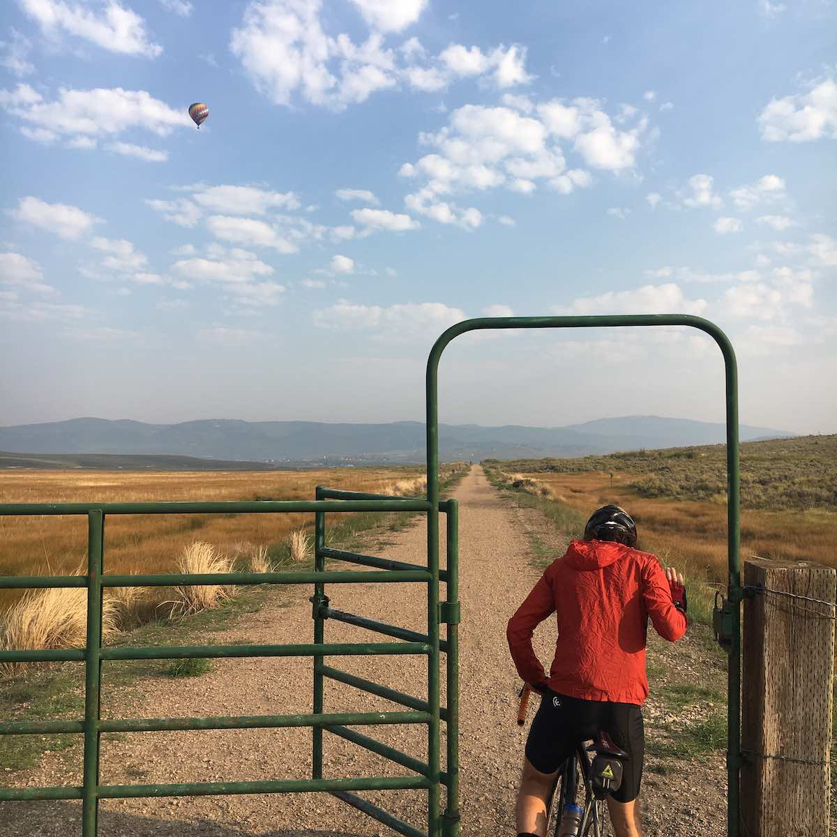 bikerumor pic of the day a cyclist passes through a livestock gate to access a gravel road that runs straight as far as the eye can see, there are a smattering of fluffy clouds in the sky as well as a hot air balloon in the distance.