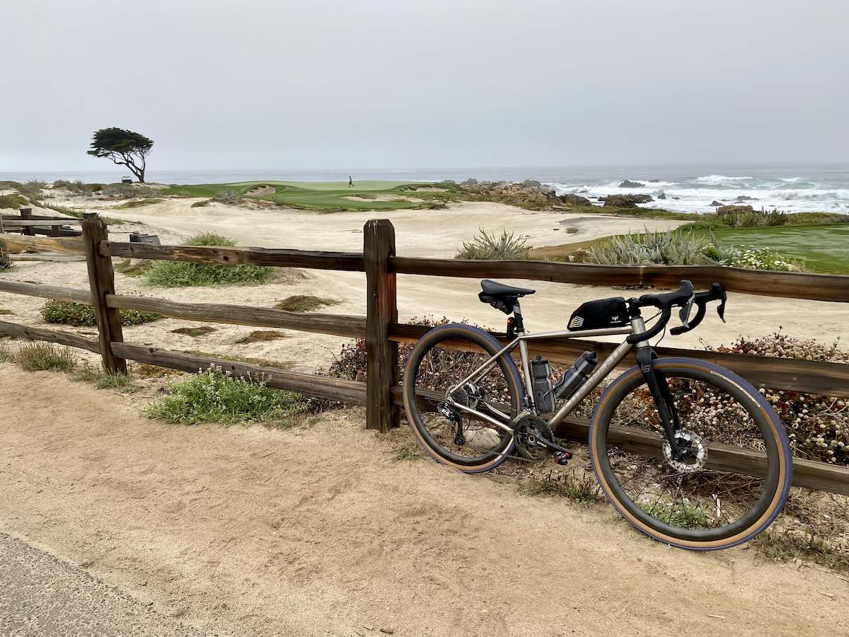 bikerumor pic of the day a bicycle leans against a wooden fence looking out over a sandy dunes and the edge of a golf course. a lone cypress tree is in the distance with the ocean beyond that, the sky is grey and hazy in the early morning light.