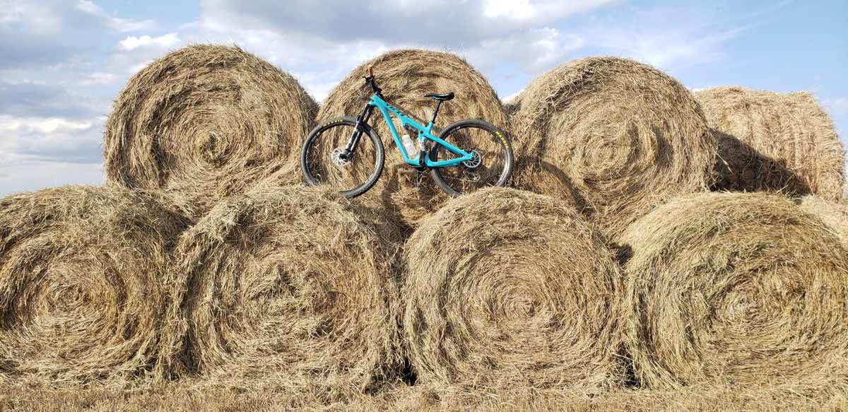 bikerumor pic of the day a bicycle sits atop a stack of round hay bales on a partially sunny day.