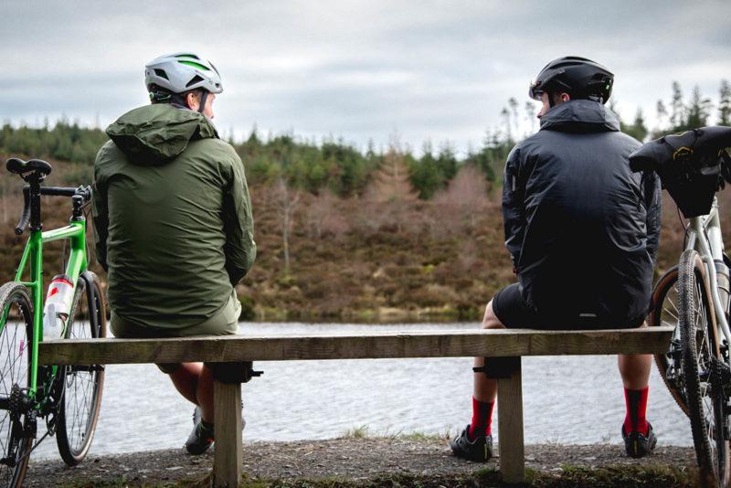 two men wearing endura gv500 coats sit facing the water next to bicycles