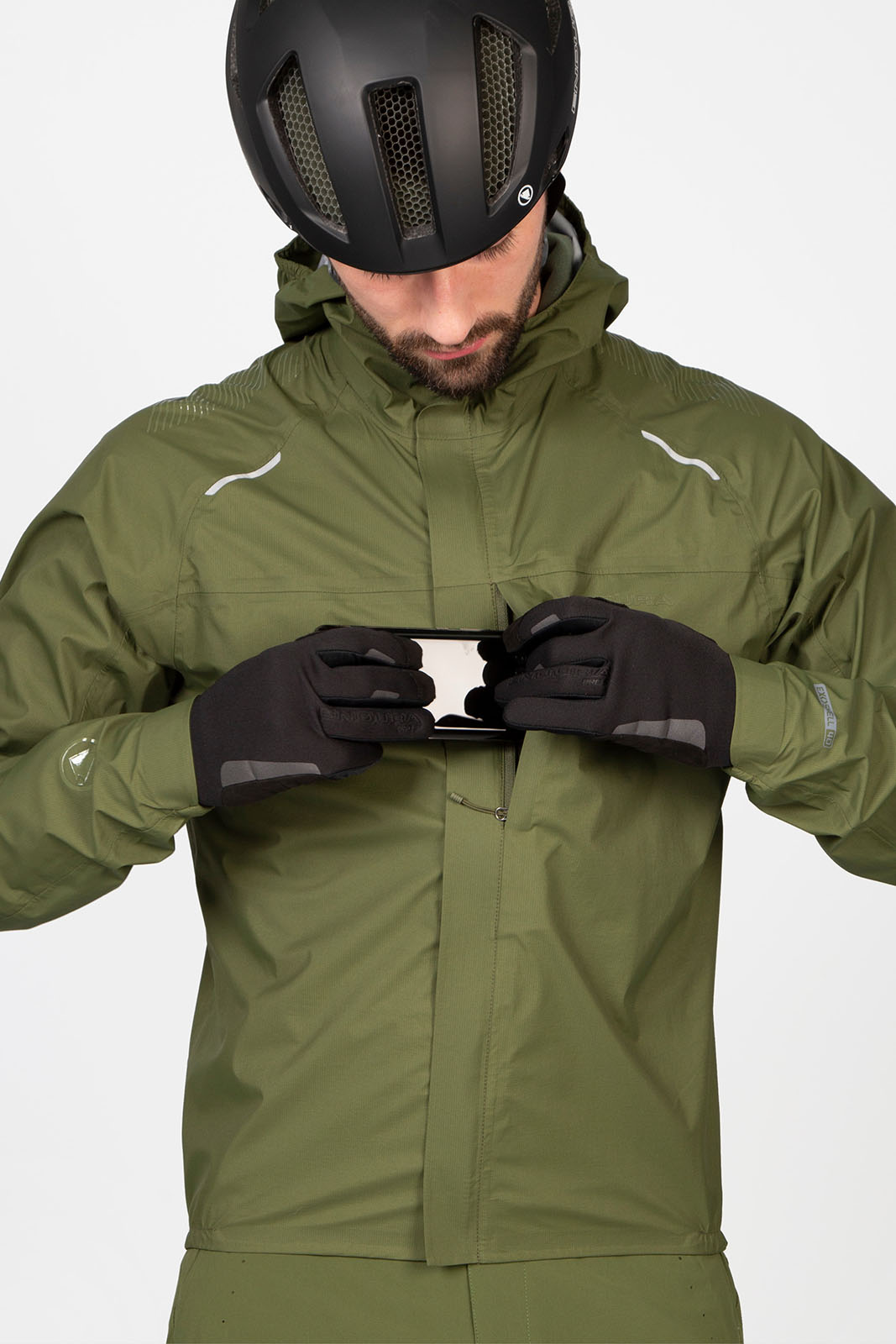 a man wearing an enduro gv500 jacket puts a phone in his pocket