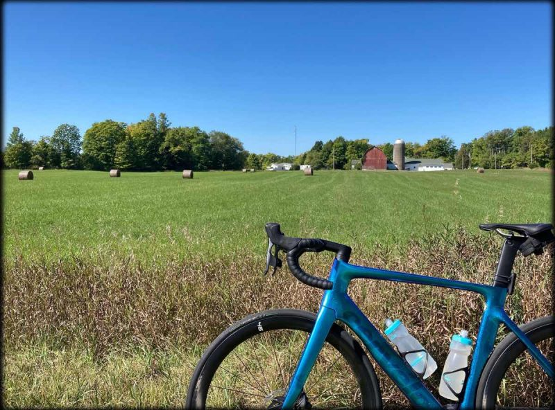 bikerumor pic of the day a blue road bicycle is positioned in front of a green grassy field with bales of hay in the distance and a red barn at the treelike. the sky is clear and blue and the sun is high.