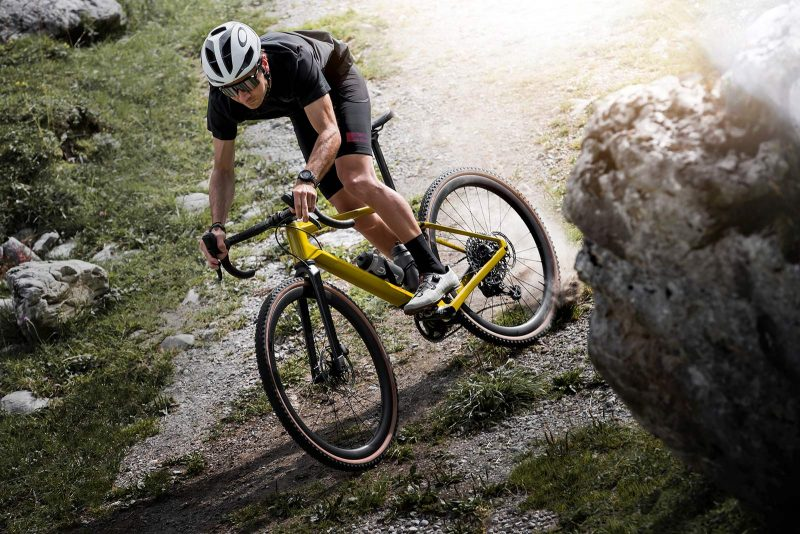 bmc urs lt full suspension gravel bike being ridden down a hill