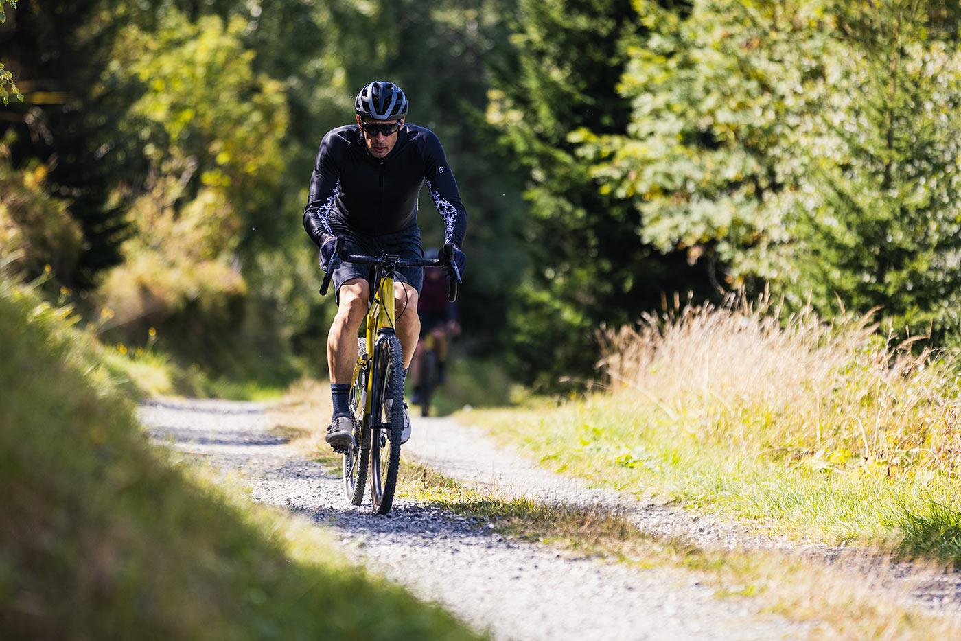 riding the bmc urs lt full suspension gravel bike on a gravel road