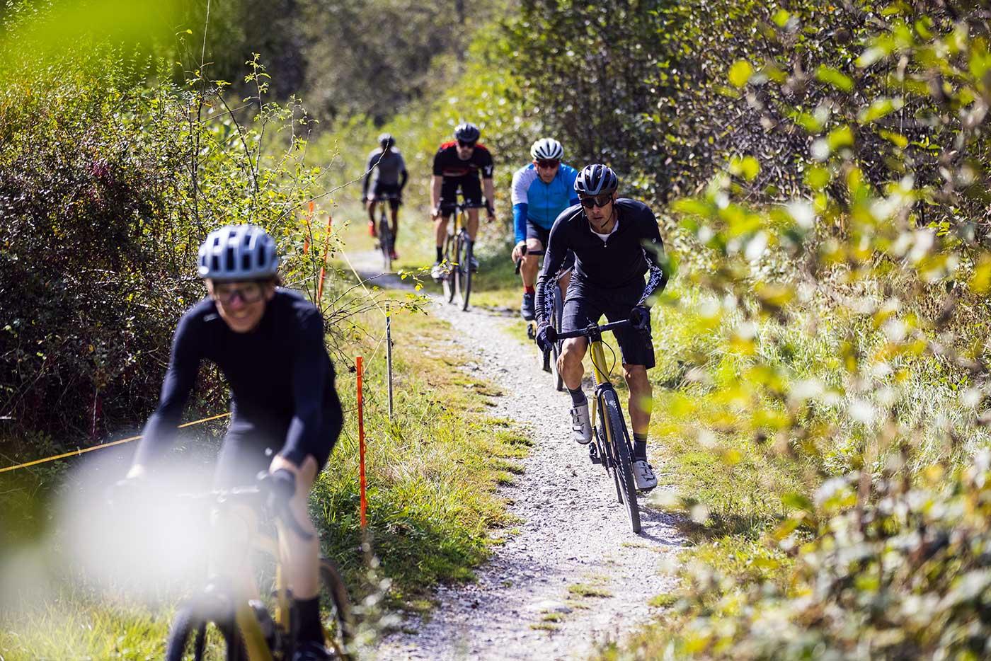 riding the bmc urs lt full suspension gravel bike on a trail
