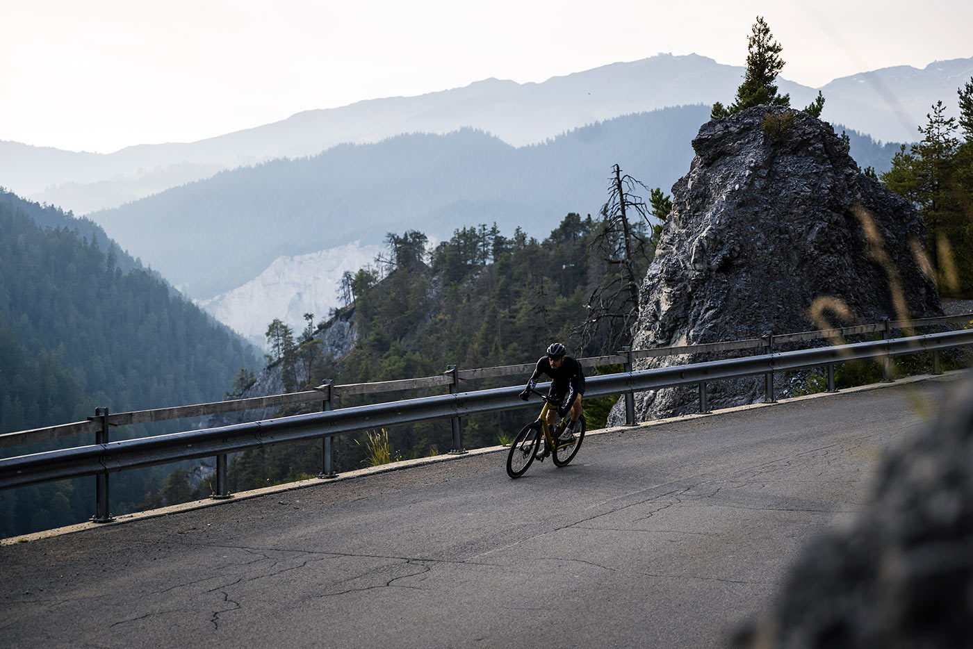 riding the bmc urs lt full suspension gravel bike on a paved mountain pass in switzerland