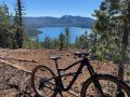 bikerumor pic of the day a mountain bike is positioned near an opening between the pine forest lookin gout onto a crater lake, the sky is clear and the sun is high in the sky.