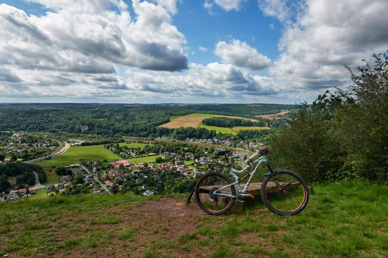 bikerumor pic of the day a mountain bike on a grassy clearing looking out over a verdant valley with a small village, the sky has fluffy white clouds with peeks of blue sky and the sun is high and bright.