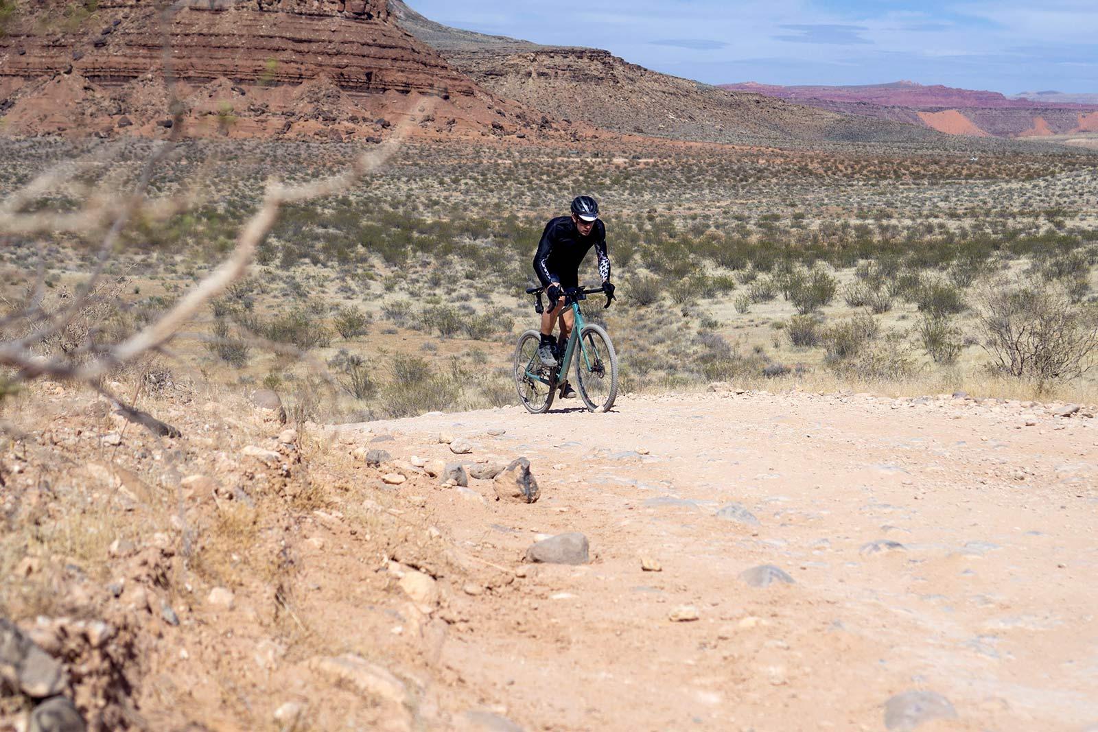 fezzari shafer gravel bike being ridden up a dirt road climb