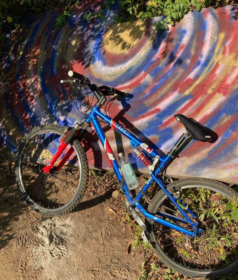 bikerumor pic of the day a blue K2 mountain bike with red fork leans against a concrete wall with a spray painted swirl design with the same colors.