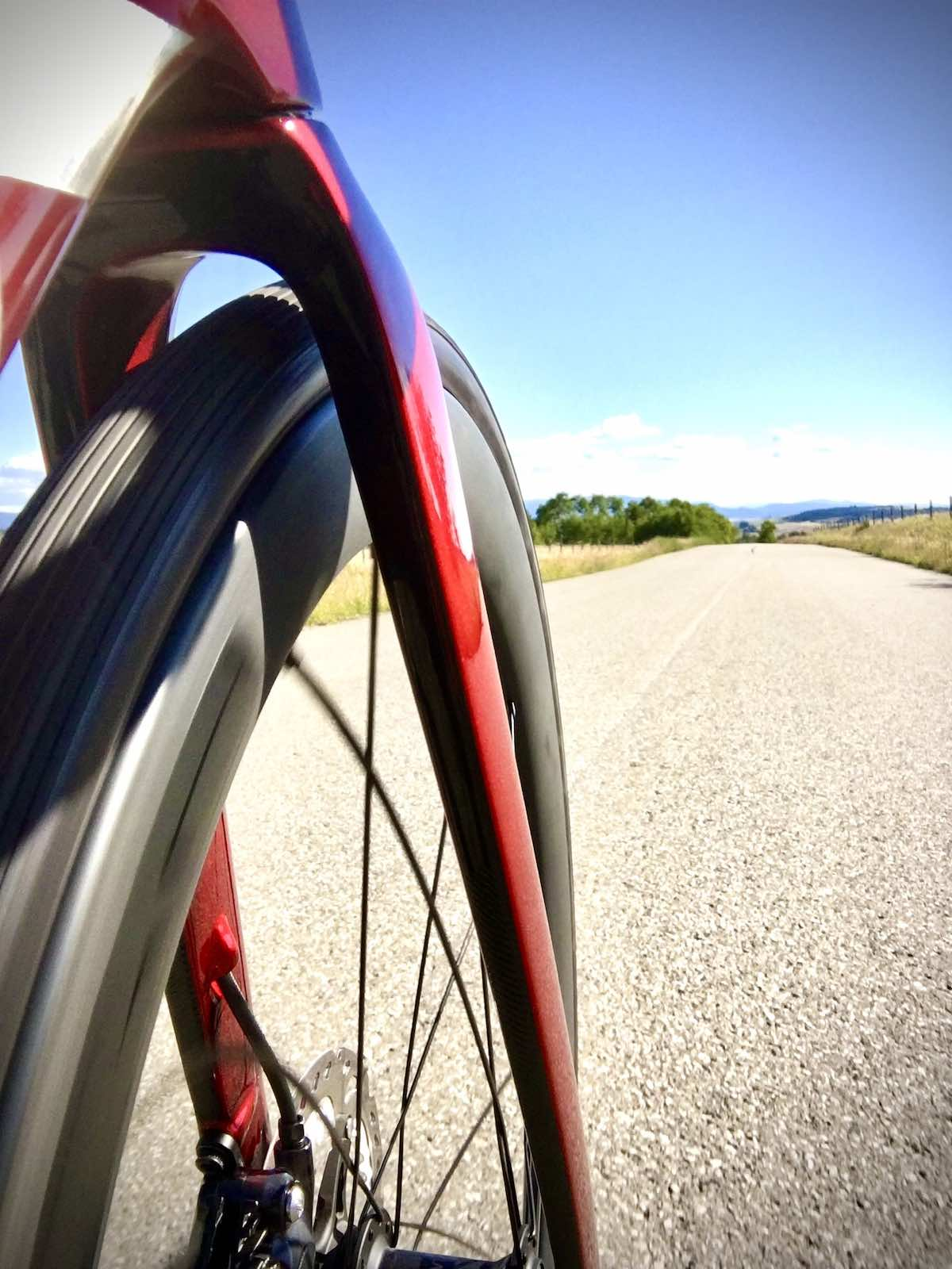 bikerumor pic of the day the photo is from the side of a road bike looking forward past the front wheel and fork towards the long straight road, the sky is clear and the sun is bright.