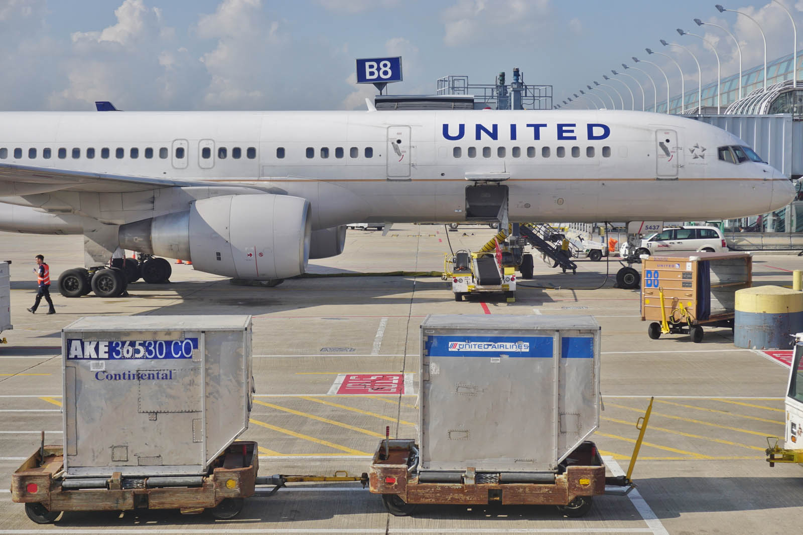 A United Airlines plane sits on the tarmac with baggage containers in the foreground