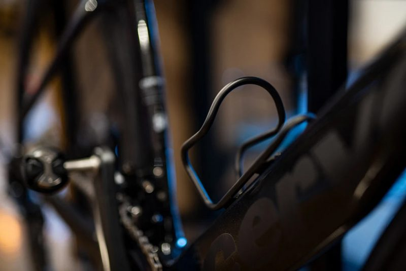 silca sicuro black cerakote titanium bottle cage mounted on a road bike