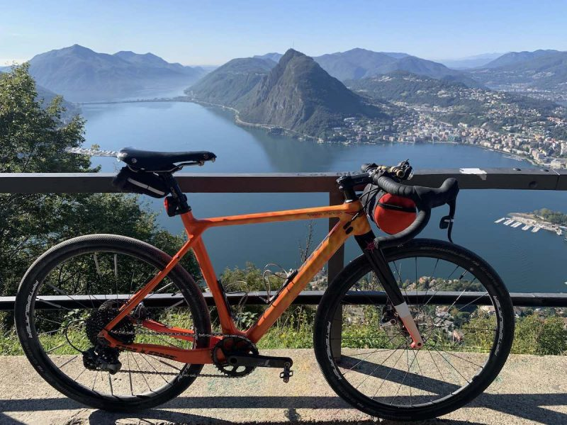 bikerumor pic of the day an on one space chicken gravel bicycle leans against a metal barrier overlooking lake lugano in switzerland.
