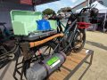 benno boost e-cargo bike with studded mountain bike tires and overlanding setup with stove and axe