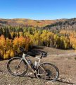 bikerumor pic of the day a bicycle is on a dirt clearing on the side of a low mountain, trees surround and have turned yellow for autumn, the sky is clear and blue.
