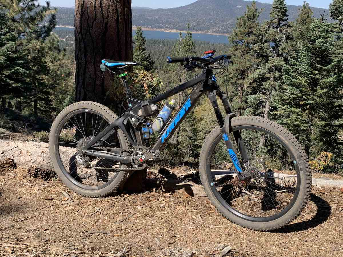 bikerumor pic of the day a mountain bike is on a dit trail next to a large tree trunk, the view beyond the tree are pine trees on the side of the mountain with a view of a lake far away, the sun is bright.
