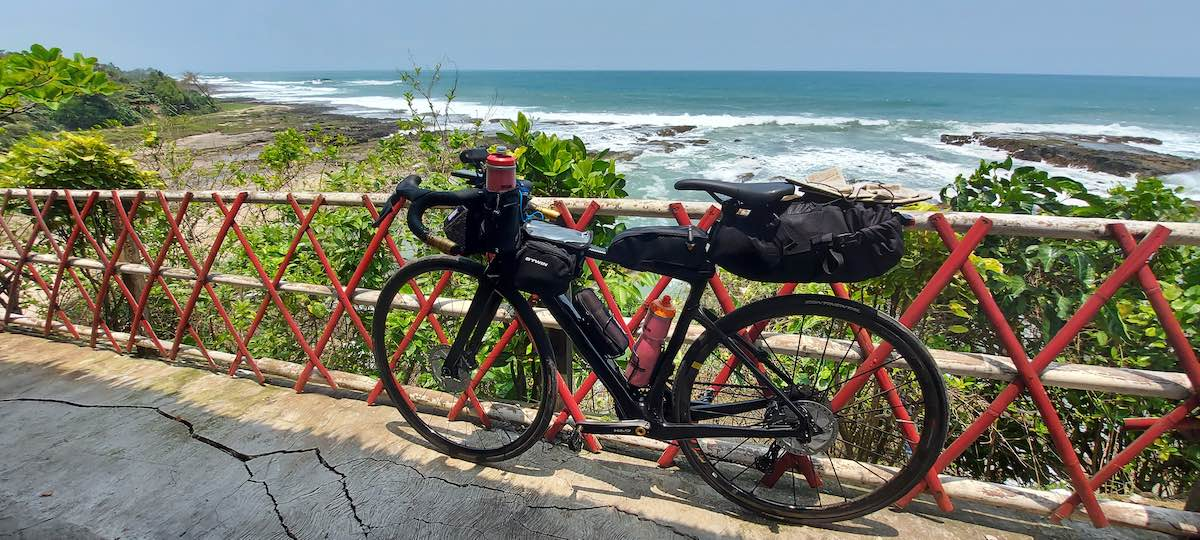 bikerumor pic of the day a gravel bike is packed with gear for a long distance race, it is leaning against a red fence barrier overlooking a rocky beach on the southern edge of indonesia, the sun is bright and the sky is clear.