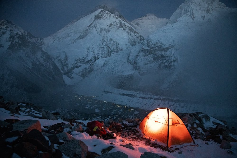 A light tent at night looking toward Everest
