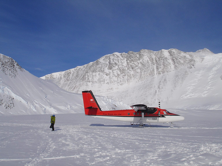 Bush plane surrounded by snowy mountains