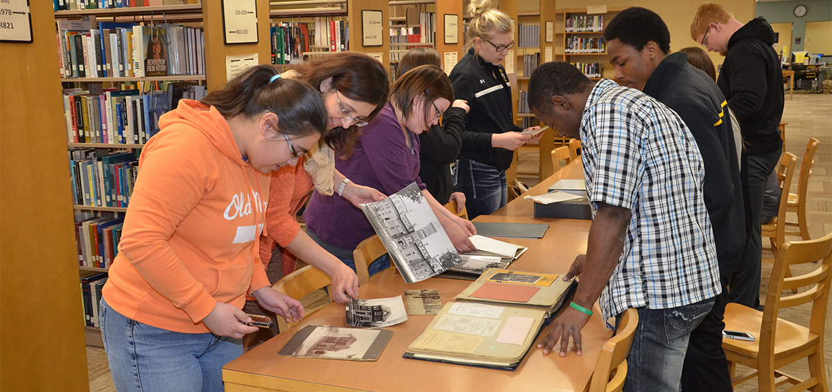 ECC students looking through old photos in ECC library