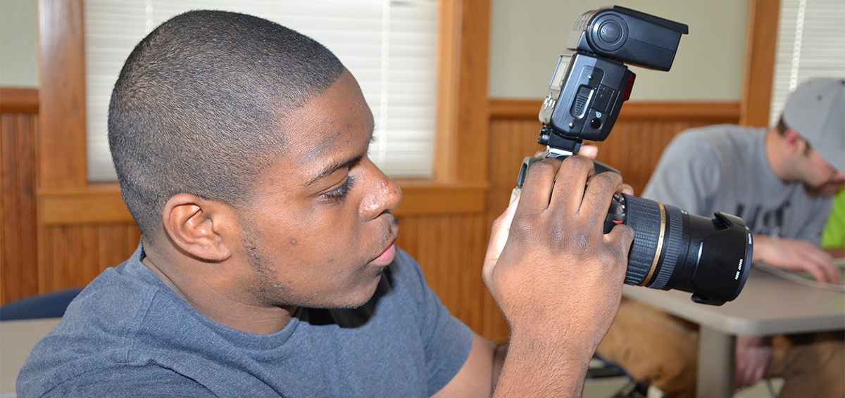 ECC student looking through cameral lens
