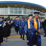 Graduates are cheered by faculty and staff.