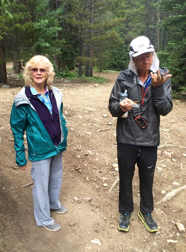Andrew with his mom Brenda on Day 7, inspecting his hands which are raw from scrambling (Laura Hamilton)