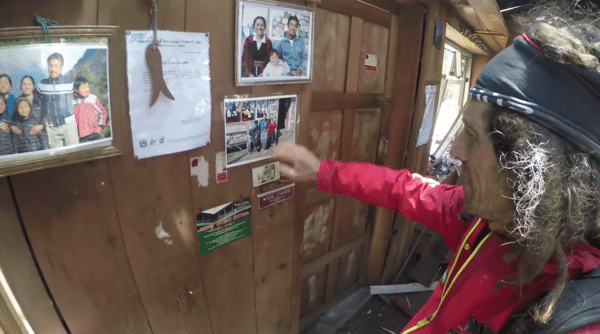 Jordi Tosas looks at pictures of people he knows in Langtang Valley