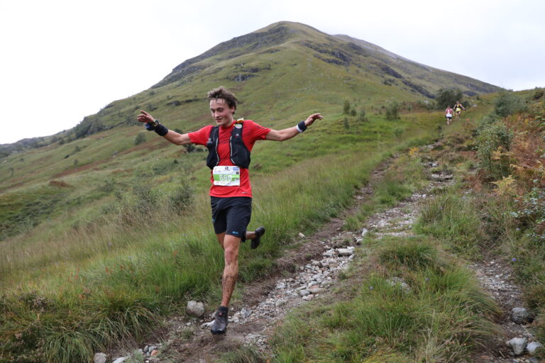 A runner descending on a rainy day during the Ring of Steall Skyrace.