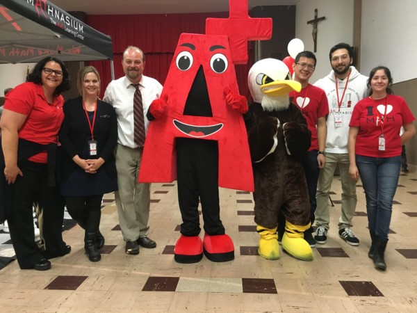 Mathnasium mascot posing with school staff and school mascot